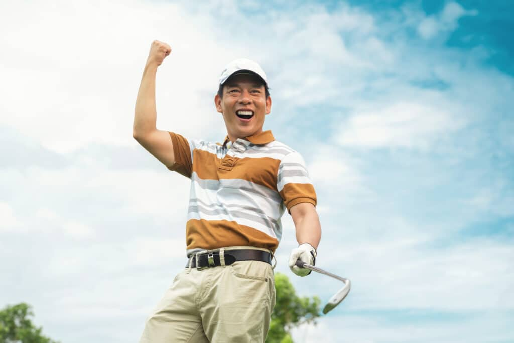 Fist pump in excitement after a great golf shot